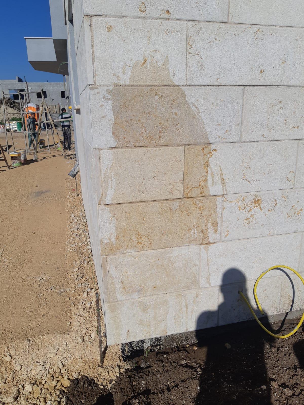 מריחה של דוגמת סקרמו טרצה על קיר אבן והרטבה